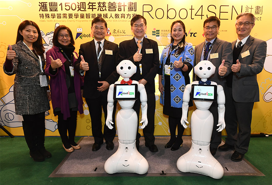 Government officials and HSBC senior executives pose with a robot as part of the Robot4SEN project