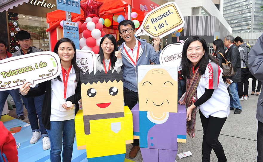 Five HSBC volunteers pose with two cardboard cutouts of cartoon people at the annual Hong Kong Community Festival